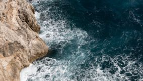 Birds eye view of rough ocean coastline, white waves. A birds eye view of a stony shore line with rough blue and white ocean waves Royalty Free Stock Images