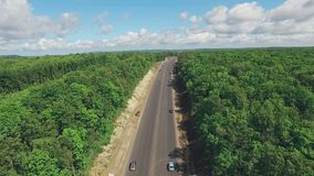 Birds eye view of a rural in Russia, camera moving above modern road. Dense forest, vivid white clouds, sunny summer day HD stock footage