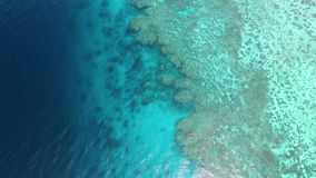 A deep blue ocean and coral reef. A birds eye view of the sea and coral reef underwater. Shot shows a boat on the ocean. Aerial shot. Shot increases altitude to stock video