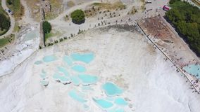 Birds eye view of thermal springs located on white limestone terraces. Fly over the travertines in Pamukkale, Turkey. 4k stock footage