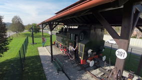 Birds eye view of a vintage steam train. Slow motion RAW helicopter camera flaying above the couple who is climbing on the steam train on a sunny day stock video footage