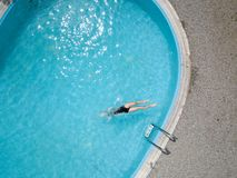 Birds eye view, young girl in black swimsuit, jumps into a swimming pool. Royalty Free Stock Image