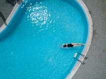 Birds eye view, young girl in black swimsuit, jumps into a swimming pool. Royalty Free Stock Photo