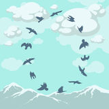 Birds in flight over the mountain tops Stock Photos