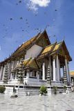 Birds fly over the main chapel of Wat Suthat in Ba Royalty Free Stock Images