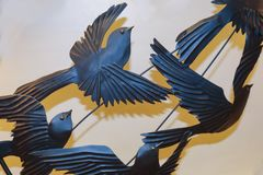 Birds flying in freedom - small detail of metal decor with shadows against wall royalty free stock image