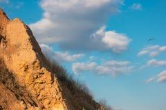 Birds flying near a mountain. Cloudy sky and rock. Sense the freedom. Long way to the goal Stock Photos