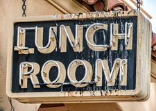 Lunch room sign, bird perch. Birds have been busy on a lunch room neon sign stock image