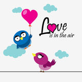 2 birds with heart and love message. 2 birds with 1 bird holding heart shaped balloon Stock Photo