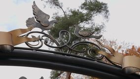 Birds made of metal on the gate look at each other stock footage