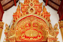 Birds and patterns in old style of royal Thailand at carved decoration over the entrance in traditional Buddhist temple Stock Photos