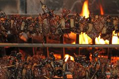 Birds and roasts on a spit in the fireplace with the flame lit Stock Photo