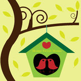 Birds in tree house birdhouse. Two little love birds kissing in their birdhouse hanging from a tree with falling leaves Stock Images