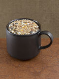 Birdseed in a brown mug Royalty Free Stock Images