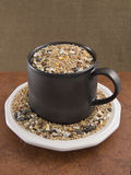 Birdseed in a brown mug and saucer Royalty Free Stock Photography