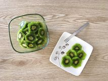 Ripe Sliced Kiwi with Light Oak Wood Background. Birdseye view of fresh organic cut kiwis in a modern clear glass bowl with more sliced kiwi on an appetizer stock images