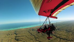 Birdseye view overlooking gliders, sea, land. Birdseye view from mounted camera overlooking hanglider, sea and land stock video footage