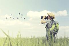 年轻birdwatcher看与他的双筒望远镜鸟世界 免版税库存图片