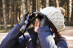 Birdwatcher. Woman aged 25-30 - looking through a pair of binoculars at birds in the trees Stock Photo