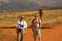 Birdwatchers trekking in South Africa. Elderly father and adult son, both overweight, trekking and observing birds and wildlife stock images