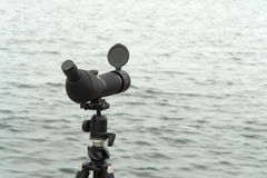 Birdwatching spotting scope monocular on a tripod near the water Royalty Free Stock Photos