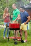 Bière potable sur la partie de barbecue Photographie stock libre de droits