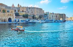 Maltese water taxi, Birgu, Malta. BIRGU, MALTA - JUNE 17, 2018: The dghajsa water taxi is traditional Maltese wooden boat, offering pleasant trips along Valletta Stock Photo
