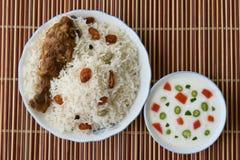 Biriyani del pollo con con la inmersión del yogur en lado Imagen de archivo libre de regalías
