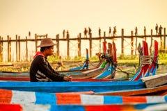 Birmański barkarza czekanie dla pasażera przy U Bein mostem, Taung Tha Mężczyzna jezioro w Amarapura, Mandalay, Myanmar Fotografia Royalty Free