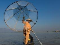 Birmański rybak opiera na wiośle pozuje w tradycyjnym odziewa z ręką i stopą trzyma jego szyszkowa kształtna sieć rybacka zdjęcia royalty free