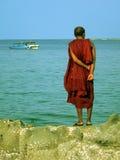 Birma. Monnik die zich op Rots bevindt stock afbeelding