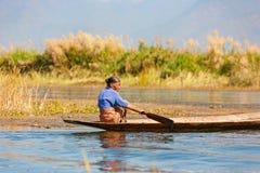 Birmaanse oude vrouw op traditionele boot op Inle-meer, Myanmar stock fotografie