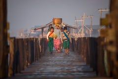 Birmanische Familie geht nach Hause vom Markt entlang hölzernem Steg bei Sonnenaufgang Lizenzfreie Stockfotografie
