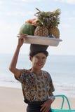 Birmanische Frau, die frische Früchte an der Küstenlinie an Touristen in Ngapali-Strand verkauft myanmar Stockbild