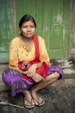 Birmanische Frau, die vor der Tür sitzt Lizenzfreie Stockfotos