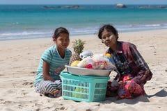 Birmanische Frauen, die frische Früchte an der Küstenlinie an Touristen in Ngapali-Strand verkaufen myanmar Lizenzfreies Stockbild