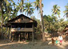 Birmanische Kinder, die zwischen traditionelle Bambushäuser in einem Dorf gehen lizenzfreies stockfoto