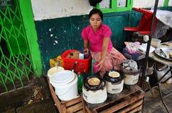 Birmanische Leute, die Lebensmittel für Verkauf an Rangun-Markt kochen Stockbild