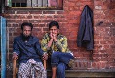 Birmanische Männer, die am alten Backsteinhaus sitzen stockfotos