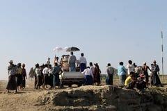 Birmanische Männer, die ein allgemeines Boot entladen Stockfotografie