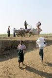 Birmanische Männer, die ein allgemeines Boot entladen Stockbild