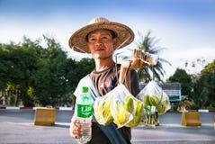 Birmanischer armer Mann, der herein Straßenfrüchte und -wasser auf Pyay-Straße verkauft stockfotos