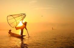 Birmanischer Fischer auf anziehenden Fischen des Bambusbootes lizenzfreie stockfotos