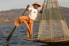Birmanischer Fischer auf anziehenden Fischen des Bambusbootes auf traditionelle Art mit handgemachtem Netz Inle See, Myanmar, Bir Stockbild
