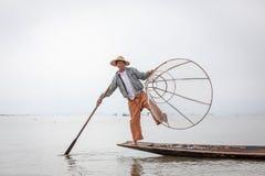Birmanischer Fischer, der für Touristen in einem traditionellen Fischerboot am Inle See, Myanmar Birma aufwirft stockbilder