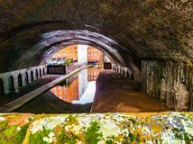 Birmingham Canal. Reflection of building in waters of canal through underbridge with moss and great texture overall Royalty Free Stock Image