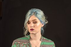 Caucasian female model, Age 22, Blue dyed hair, Red lips, green and red shirt. Isolated on black background. Head and shoulders royalty free stock photography