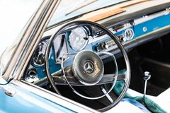 BIRMINGHAM, UK - March 2018 Steel Plated Steering Wheel with Logo Symbol and Dashboard of Vintage Car. Closeup Interior royalty free stock photo