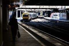 BIRMINGHAM, UK - March 2018 Two Trains One is Parked the Other Arriving or Leaving. Silhouette of Person Walking on the. Platform. Ticketing Office on the stock photo