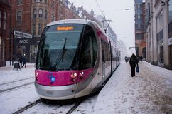 Tram during heavy snowfall in Birmingham, United Kingdom. Birmingham, United Kingdom - March 02 2018 : Tram arriving at railway station during heavy snowfall in stock images